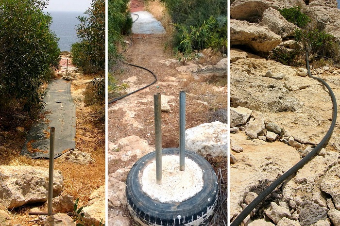 Fældeområde dækket af tæpper, betonfyldte dæk til fastgørelse, vandingssystem til akacier