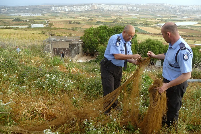 Maltese policemen dismantle a net found by CABS volunteers